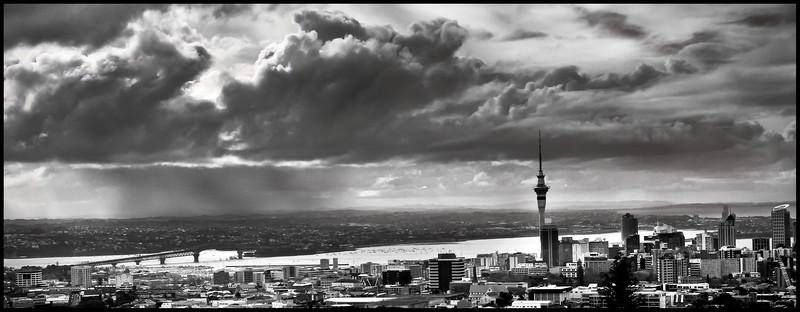 Rainclouds pour rain over Auckland's North Shore. Auckland city photographed from Mount Eden