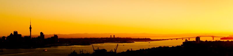 The sun sets over Auckland city and the Auckland Harbour Bridge