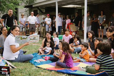 A teacher reads a book to the kids at the UpValley Family Center as the Auction Napa Valley guests watch.   Photo by Bob McClenahan for the Napa Valley Vintners