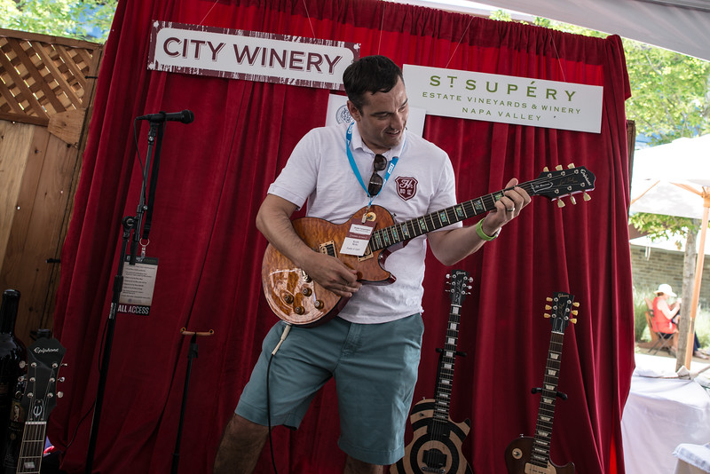 """Guests are allowed to play various guitars at the City Winery/St. Supery display at the barrel auction. <br> <br> Photo by <a href=""""http://napasphotographer.com/"""">Bob McClenahan</a>"""