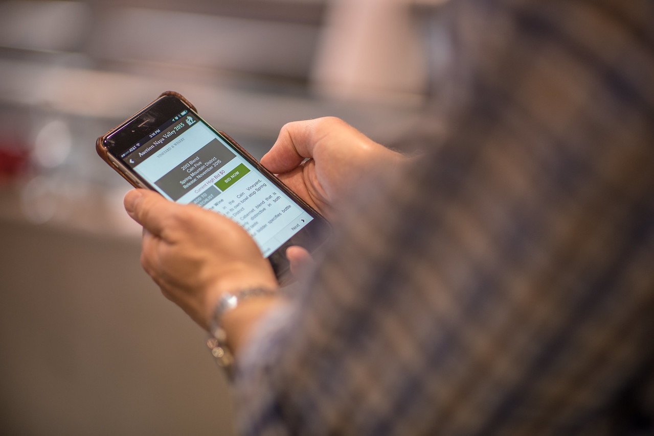 """Bidders use the Auction Napa Valley app to keep track of their lots. <br> <br> Photo by <a href=""""http://napasphotographer.com/"""">Bob McClenahan</a>"""