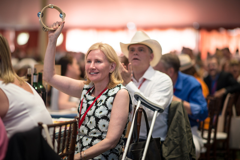 """Kary Duncan, one of the auction chairs, raises her tambourine during the live auction.  Photo by <a href=""""http://napasphotographer.com/"""">Bob McClenahan</a> for Napa Valley Vintners."""