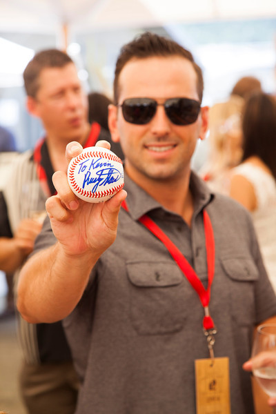 """A happy guest holds up an autographed ball by baseball legend Rusty Staub, who was helping to promote the Staglin Family Live Auction Lot. Photo by <a href=""""http://www.tinacciphoto.com"""" target=""""_blank"""">Jason Tinacci</a> for the Napa Valley Vintners."""
