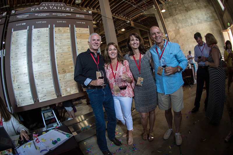 """Ed Fitts, Deb Whitman, Kelli Willard, and Greg Gregory stand in front of their board.  Brand Napa Valley was the recipient of the highest bid during the barrel auction.  Photo by <a href=""""http://napasphotographer.com/"""">Bob McClenahan</a> for Napa Valley Vintners."""