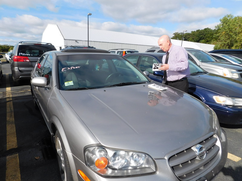 Auctioneer Stanley J. Paine placing numbers on cars for Saturday's auction.