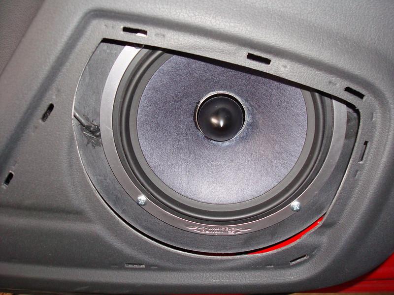 Aftermarket speaker viewed through speaker grill