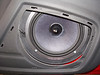 Aftermarket speaker viewed through speaker grill
