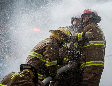 Erath Volunteer Fire Department firefighters aim their water hoses as they are sprayed by Delcambre Fire Department firefighters during the annual Erath firefighter water fights in downtown Erath, La., Saturday, July 4, 2015.