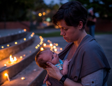 Kate Lemoine holds her newborn daughter Harlan Hawkins as she has a moment of reflection during a candlelight vigil for the victims of the Grand 16 Theatre Shooting at Parc Sans Souci in Lafayette, La., Saturday, July 25, 2015.
