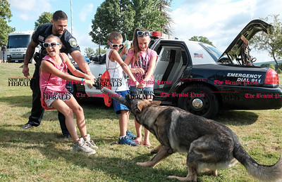 080216  Wesley Bunnell | Staff  New Britain Ofc. Ray Ouellette and his K9 partner Pup engage in a game of tug and war with the help of siblings from L Mikalah Baez, age 11, Andres Baez, age 7, & Mya Baez, age 10.  National Night Out took place on Tuesday Aug 2nd from 5-7pm at Walnut Hill Park. The event is part of a community-police awareness event across the country to strengthen common bonds.