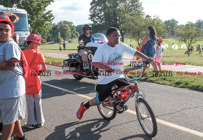 080216  Wesley Bunnell | Staff  Rudolph Joseph, age 11, rides his bike next to a New Britain motorcycle officer. National Night Out took place on Tuesday Aug 2nd from 5-7pm at Walnut Hill Park. The event is part of a community-police awareness event across the country to strengthen common bonds.