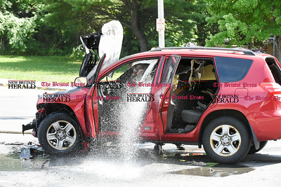 080916  Wesley Bunnell | Staff  Firefighters douse a Toyota Rav 4 with water just before being towed away from the scene of an accident. Two cars collided at the intersection of North & Stanley St on Tuesday afternoon. A Toyota Rav 4 with two occupants caught fire after the occupants were able to exit the vehicle and brought to the hospital for care. The driver and sole occupant of the other car, a Dodge Caravan, remained at the scene.