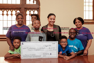 081516  Wesley Bunnell | Staff  The children of Shenia Walker present a check for $200 to the Prudence Crandall Center on Monday afternoon. From L Mario Walker age 5, Nasir Walker age 12, Amari Walker age 4 & Naseem Walker age 9. In the back row is Shenia's aunt Tammy  Walker, grandfather Penny Walker, aunt Ashley Walker & grandmother Pat Walker. The children lost their mother Shenia in 2013 to domestic violence.