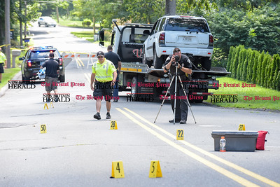 081516  Wesley Bunnell | Staff  A Southington police officer takes photographs of evidence on Savage St in Southington on Monday afternoon. A pedestrian was struck and killed by the Chevy Trailblazer being towed in the background.