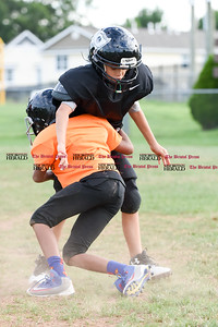081716  Wesley Bunnell  | Staff  Omarion Figueroa in black being blocked by David Lockhart during the New Britain Police Athletic League's Raider Junior Pee Wee D team practice. PAL, held cheerleading & football practice on Wednesday evening at Al Beatty Memorial Field.