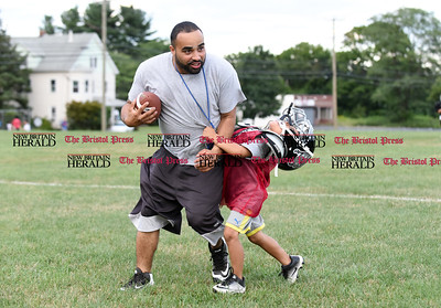 081716  Wesley Bunnell  | Staff  Coach Miguel Merced of the New Britain Police Athletic League is held up by player and son Miguel Merced Jr during practice. PAL, held cheerleading & football practice on Wednesday evening at Al Beatty Memorial Field.