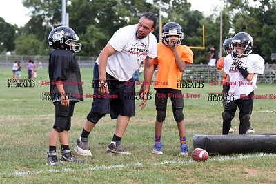 081716  Wesley Bunnell  | Staff  Coach Marcus Campbell showing proper technique to members of the the New Britain Police Athletic League's Raiders Junior Pee Wee D team. PAL, held cheerleading & football practice on Wednesday evening at Al Beatty Memorial Field.  Players from left include Ethan Riviera, David Lockhart & Joshua Kaniel.