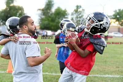 081716  Wesley Bunnell  | Staff  Coach Miguel Merced of the New Britain Police Athletic League Tiny Mites Raiders football has the ball stripped by Jonathan Martinez. PAL, held cheerleading & football practice on Wednesday evening at Al Beatty Memorial Field.