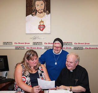 082216  Wesley Bunnell | Staff  From left Sacred Heart School Principal Katherine Muller, Sister Mary Janice Zdunczyk and Monsignor Daniel Plocharczyk look over documents related to the upcoming open house.  Sacred Heart is holding an open house Wednesday evening from 5pm to 8pm for prospective students in the wake of the recent closing of St. Mary School in Newington.