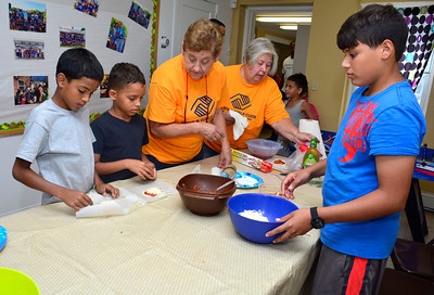 8/23/2016 Mike Orazzi | Staff Bristol Garden Club members Sue King and Claudette Dekoe make small pizzas with Bristol Boys and Girls Club children, Francisco Mendez, Jariel Pizarro and Johnny Figueroa in Cambridge Park Tuesday afternoon.  ** stand alone ***