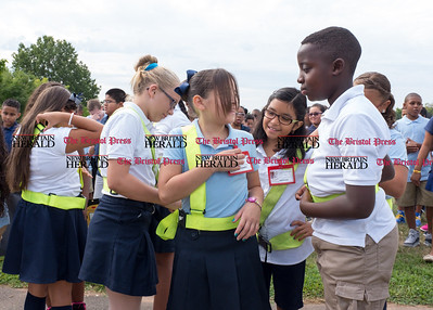082916  Wesley Bunnell | Staff  Natalka Supinski, second from left, helps fellow students adjust their Safety Patrol sashes during a ceremony held at Smith School on Monday morning. 5th grade students received their AAA Safety Patrol sashes in the attendance of local school officials , police and a AAA representative.