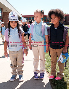082916  Wesley Bunnell | Staff  Kindergarten students leave Smith Elementary School ready to board buses for the ride home on Monday afternoon after their first day of school. Students wore hats reading I Rocked My First Day of School.