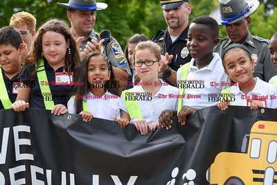 082916  Wesley Bunnell | Staff  Representatives from the CT State Police and the New Britain Police Department applaud as Smith School students receive their Safety Patrol sashes in a ceremony on Monday morning. The students are holding a banner promoting safety from the AAA.