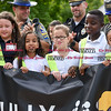 082916  Wesley Bunnell | Staff<br /> <br /> Representatives from the CT State Police and the New Britain Police Department applaud as Smith School students receive their Safety Patrol sashes in a ceremony on Monday morning. The students are holding a banner promoting safety from the AAA.