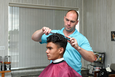 081616  Wesley Bunnell  | Staff  New owner Heath Long of Modern Barber Shop in Newington works on local 8th grader Diogo Caetano's hair on Tuesday afternoon.