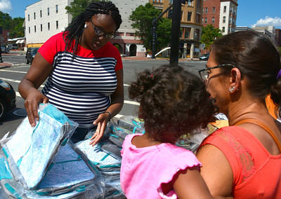 8/20/2016 Mike Orazzi | Staff Nikke Sogunro passes out school supplies in downtown New Britain during the Mama Stitches event held at Trinity on Main Saturday.