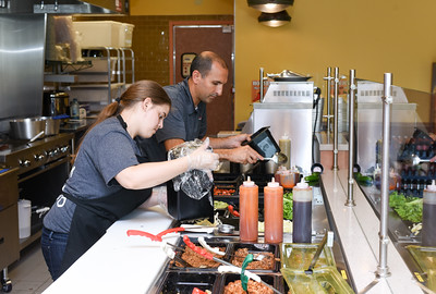 082416  Wesley Bunnell | Staff  Hot Harry's Fresh Burritos has opened in New Britain near the CCSU campus. Holly Grosberger works alongside the founder and executive vice president Samir Abdallah on the second day of business on Wednesday Aug 24th.