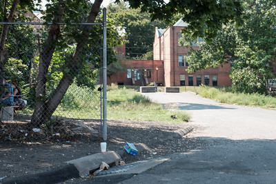 082416  Wesley Bunnell   Staff  The area behind Friendship Service Center on Arch St in New Britain shown on Wednesday afternoon.  Looking past the bench area on the left where locals and homeless congregate the area at top near the cinder blocks is believed to be where the shooter was located in last Friday's shooting of Angela Semidey.