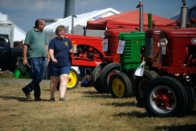 8/27/2016 Mike Orazzi   Staff Paul and Cathy Winzler walk past the antique tractors at the 68th  annual Terryville Lions Country Fair Saturday afternoon.