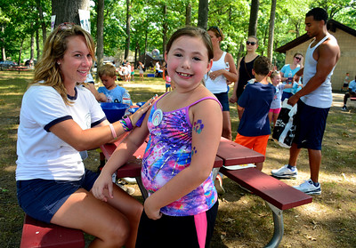 8/12/2016 Mike Orazzi | Staff Aubrey Root gets a tattoo from Shayla Beausoleil during Plainville Fun Day activities Friday at Norton Park.
