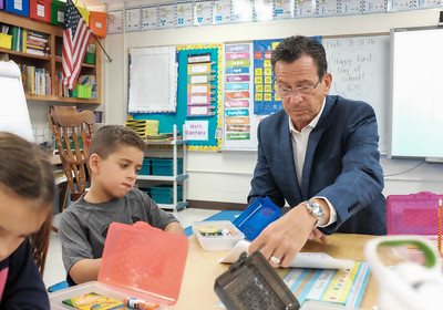 083116  Wesley Bunnell | Staff  Governor Dannel Malloy looks over school work completed by first grade student Cooper Ramirez . Governor Malloy visited Emma Hart Willard Elementary School on Wednesday Aug 30.
