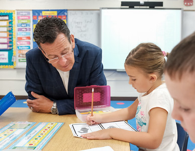 083116  Wesley Bunnell | Staff  Governor Dannel Malloy watches as first grade student Kayla Thorsell performs her class work. Governor Malloy visited Emma Hart Willard Elementary School on Wednesday Aug 30.