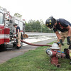 083116  Wesley Bunnell | Staff<br /> <br /> New Britain firefighter Josh Aponte, right, closes a fire hydrant at Willow Brook Park which was being used for his hands pump training on Engine 2 Wednesday afternoon. Josh who recently completed his year long probationary period is shown with Lt. Jonathan Turano.
