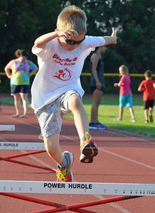 KYLE MENNIG – ONEIDA DAILY DISPATCH Luke Roberson, 6, of Sauquoit clears a hurdle during a Canastota youth track and field practice in Canastota on Wednesday, Aug. 2, 2017.