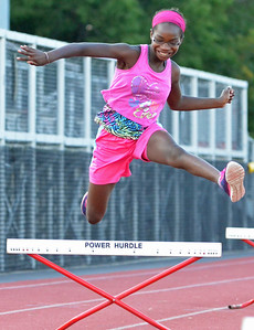 KYLE MENNIG – ONEIDA DAILY DISPATCH Jasmine Reed, 11, of Canastota clears a hurdle during a Canastota youth track and field practice in Canastota on Wednesday, Aug. 2, 2017.