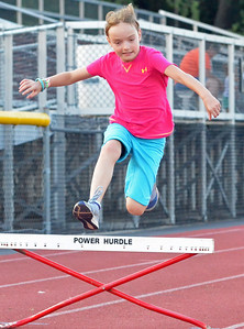 KYLE MENNIG – ONEIDA DAILY DISPATCH Olena Conrad, 10, of Canastota clears a hurdle during a Canastota youth track and field practice in Canastota on Wednesday, Aug. 2, 2017.