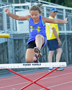 KYLE MENNIG – ONEIDA DAILY DISPATCH An athlete clears a hurdle during a Canastota youth track and field practice in Canastota on Wednesday, Aug. 2, 2017.