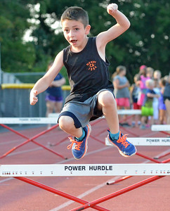 KYLE MENNIG – ONEIDA DAILY DISPATCH Caiden Smithers, 7, of Camden clears a hurdle during a Canastota youth track and field practice in Canastota on Wednesday, Aug. 2, 2017.