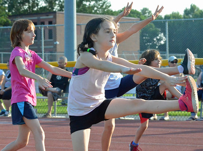 KYLE MENNIG – ONEIDA DAILY DISPATCH Athletes stretch during a Canastota youth track and field practice in Canastota on Wednesday, Aug. 2, 2017.
