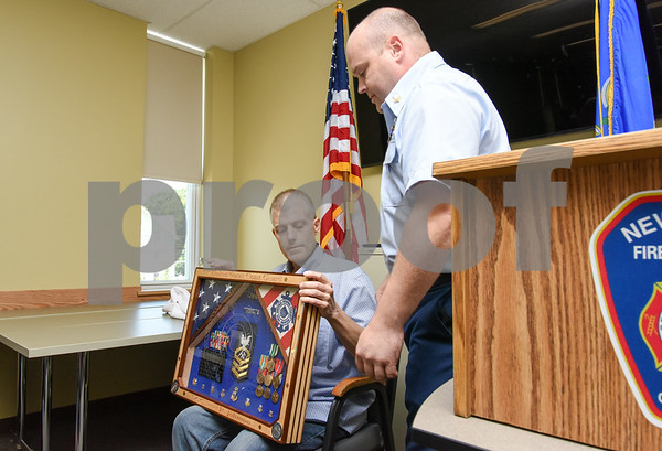 080917 Wesley Bunnell | Staff A retirement ceremony was held for Coast Guard Chief Scott Johnson at the New Britain Fire Department Headquarters on Wednesday at noon. Johnson who is battling colorectal cancer has worked as a firefighter in New Britain for approximately 10 years. Johnson looks over the shadow box which was custom made and presented by Coast Guard DC1 Wade Hinkley.
