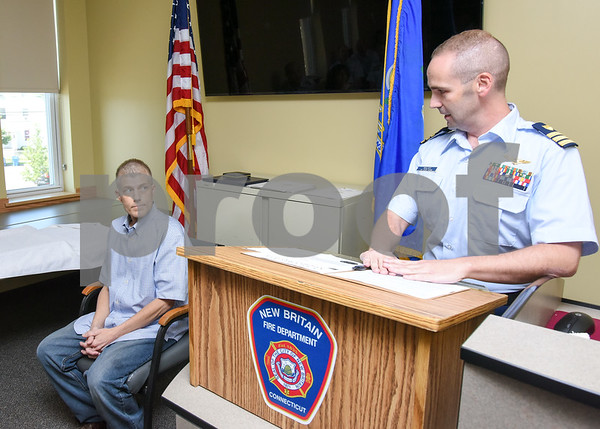 080917 Wesley Bunnell | Staff A retirement ceremony was held for Coast Guard Chief Scott Johnson at the New Britain Fire Department Headquarters on Wednesday at noon. Johnson who is battling colorectal cancer has worked as a firefighter in New Britain for approximately 10 years. Johnson, seated, listens to Coast Guard Commander Matt Walker deliver a speech.