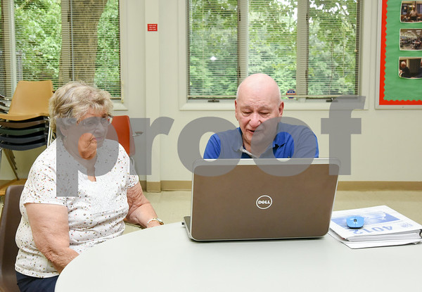 080717 Wesley Bunnell | Staff Barbara Dixon discusses her taxes with AARP Tax Aide volunteer Bruce Kraft at the Berlin Senior Center.