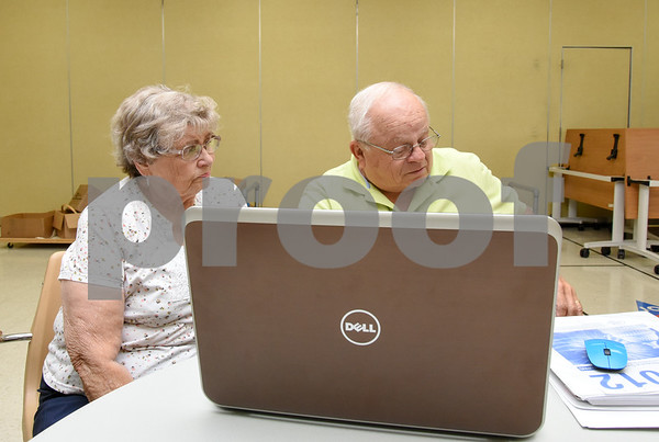 080717 Wesley Bunnell | Staff Barbara Dixon discusses her taxes with AARP Tax Aide volunteer Richard DiMinno at the Berlin Senior Center.