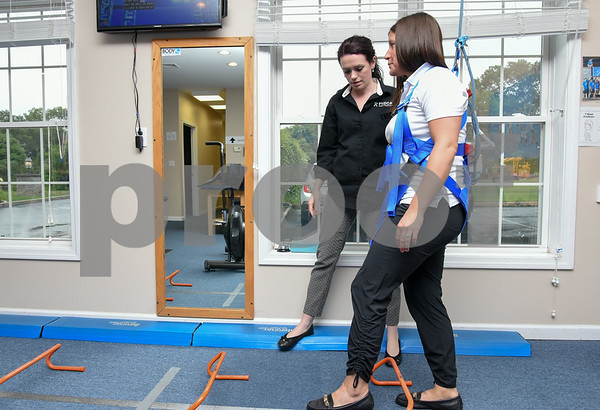 080717 Wesley Bunnell | Staff Clinical Director of the Southington Fyzical Therapy center Kaitlyn Hamel, L, puts Clinical Director of the Bristol Fyzical Therapy Center Jennifer Brester through exercises they would use with patients.