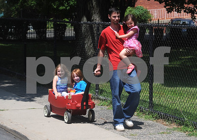 8/10/2017 Mike Orazzi | Staff Brian Saundry carries his daughter Aria while with his nieces Laighia and Riley on their way to the park on the Federal Hill green Thursday.