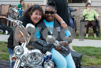 081717  Wesley Bunnell | Staff  Autumn Lake Healthcare in New Britain held a motorcycle night on Thursday for residents. Director of Nurses Annie Audette puts her arm around Shauntel Brown as Brown sits on her motorcycle and wears her vest from the Out Spoken Girls Motorcycle Club.
